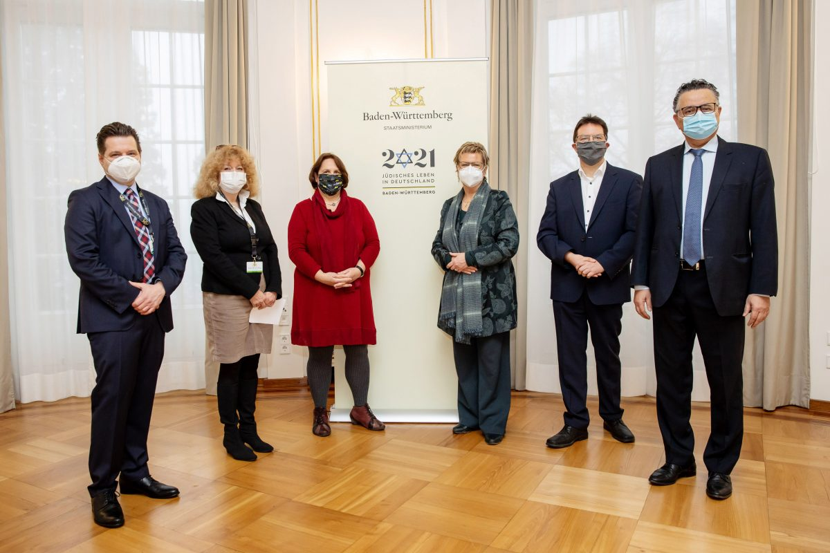 Andrei Kovacs und Sylvia Löhrmann stehen mit Ministern des Landes Baden-Württemberg vor einem Banner