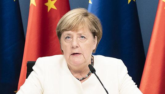 Angela Merkel auf einer Pressekonferenz vor Europaflaggen