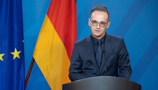 Deutscher Außenminister Heiko Maas vor Flaggen