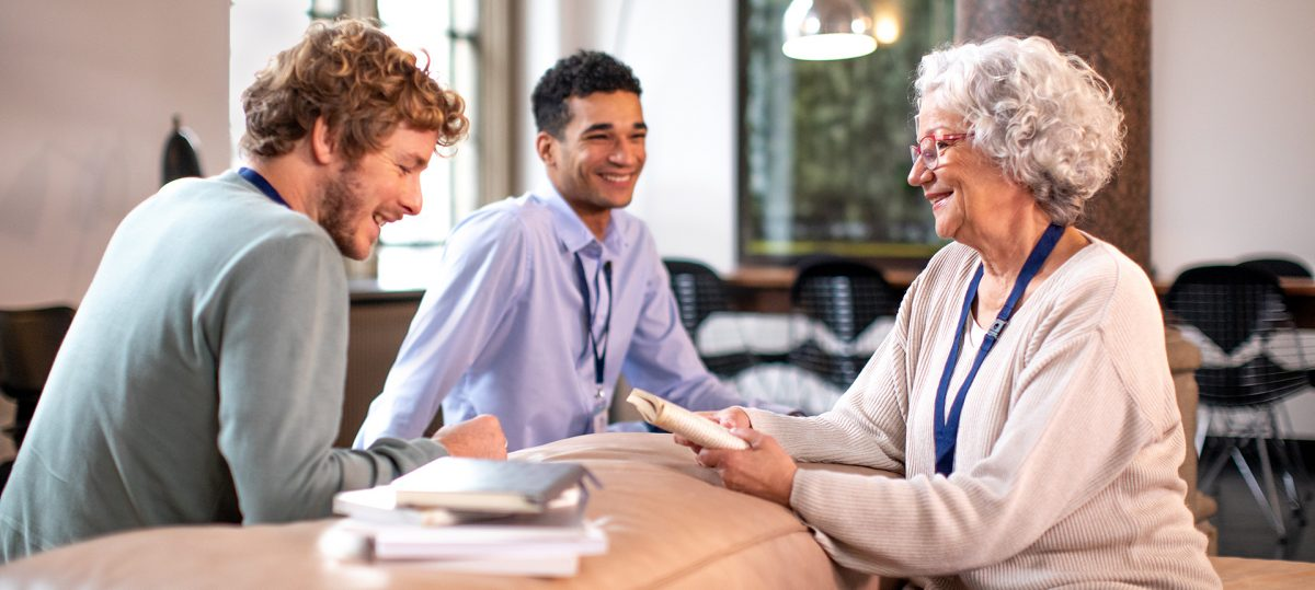 Eine ältere Fau lacht mit zwei Kollegen in Designer-Büro