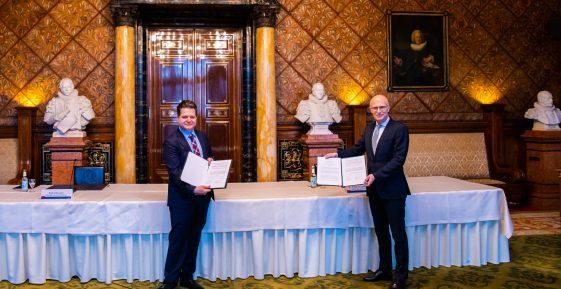 Hamburgs Bürgermeister Dr. Peter Tschentscher und Andrei Kovacs zeigen die unterzeichnete Kooperationsvereinbarung